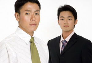 A young asian businessman standing in front of a colleague