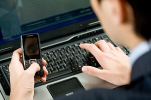 Photo of male holding cellular phone and pressing its buttons while typing on laptop keyboard